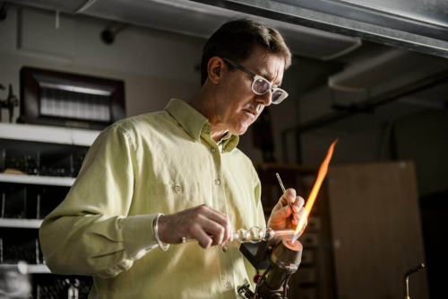 Glassblower Tracy Drier works with a flame and glassware in the 188bet体育官网 Chemistry Glass Shop