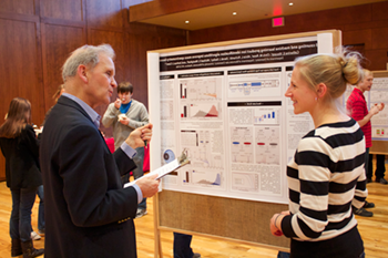 A faculty member talks to a graduate student who is presenting a poster at a graduate poster session