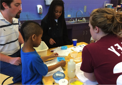 Sigma-Aldrich volunteers work with students at a sciencounters meeting