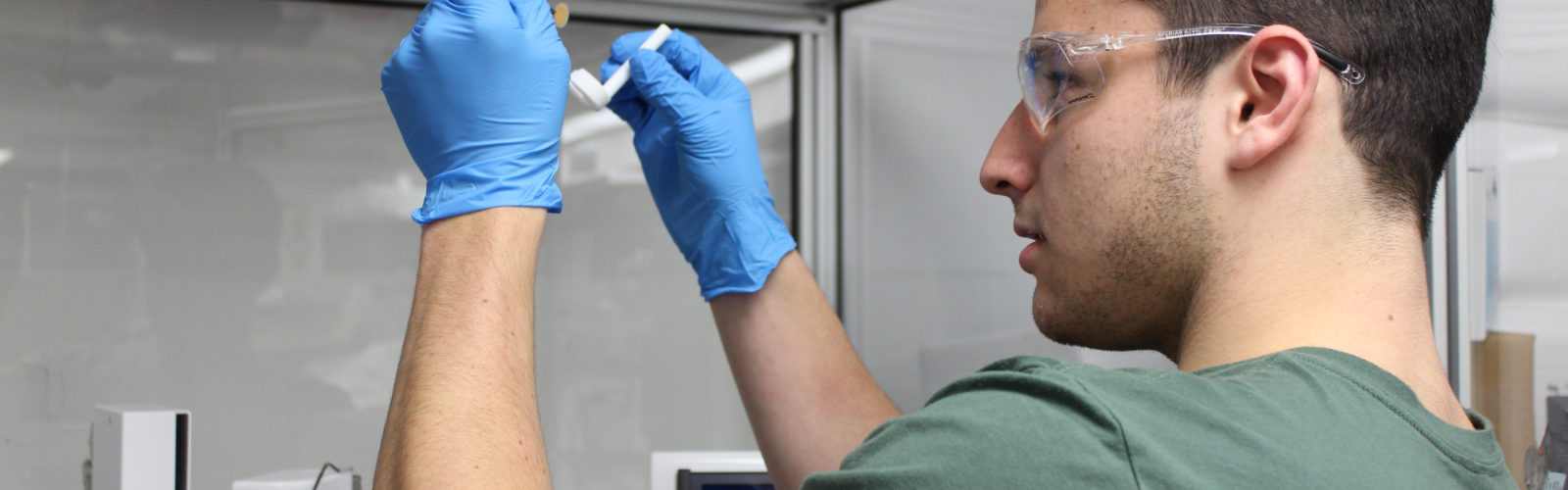 Student examining an object in a fume hood.